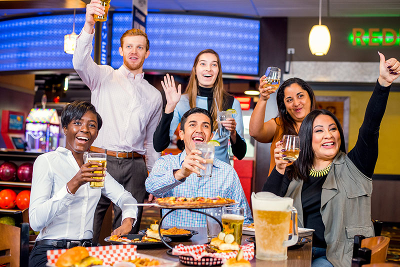 adults saying cheers | catch the game | entertainment options at super bowl entertainment center | entertainment options at sluggers sports bar and grill | appleton, wi